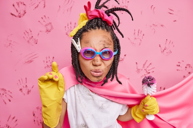 La photo d'une femme au foyer sérieuse et attentive porte des lunettes, une cape de super-héros et des gants en caoutchouc, tient une brosse pour nettoyer les toilettes occupée à des tâches ménagères isolées sur un mur rose