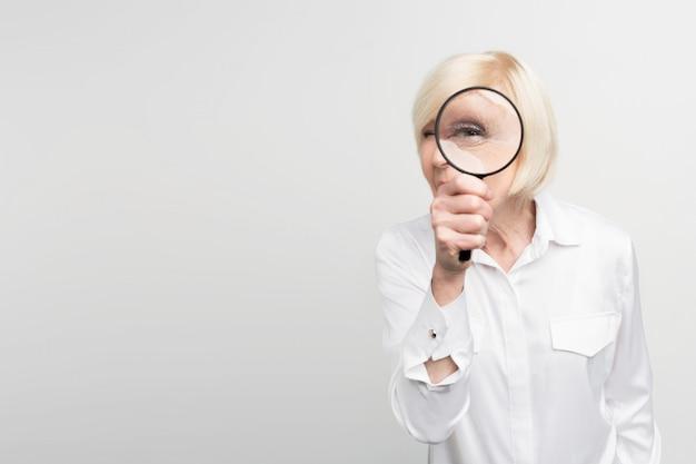 Une photo d'une femme aux cheveux blancs debout sur le côté droit du cadre et regardant droit devant la loupe.