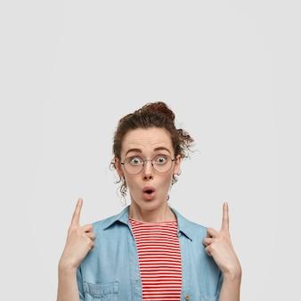 Photo d'une femme aux taches de rousseur émotive stupéfaite aux cheveux noirs, porte des lunettes rondes