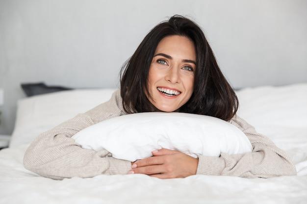 Photo d'une femme brune de 30 ans en riant, allongée dans son lit avec des draps blancs à la maison