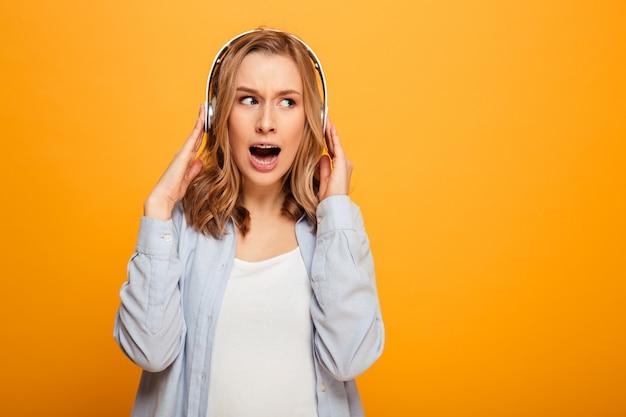 Photo d'une femme brune portant des bretelles réagir émotionnellement sur la musique tout en écoutant une chanson ou un morceau à l'aide d'un casque sans fil, isolé sur un espace jaune