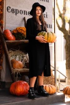Photo de femme brune posant sur fond de concept halloween avec des citrouilles. portrait de style de mode. fille portant une robe décontractée sombre et un chapeau noir.concept de mode. costume de sorcière