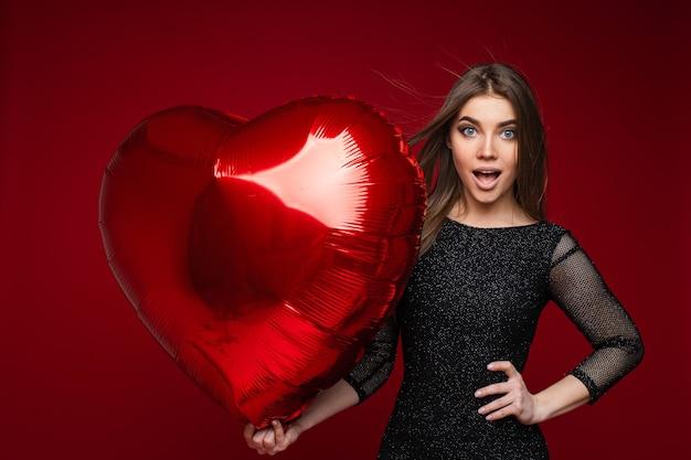 Photo de femme caucasienne surpris en robe noire avec ballon coeur dans sa main sur rouge