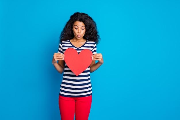 Photo de femme charmante douce à la mode en t-shirt rayé tenant grand coeur