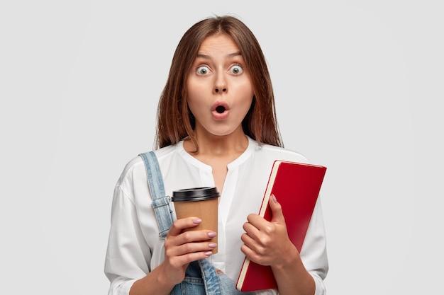Photo de femme choquée avec tasse de café et cahier dans les mains