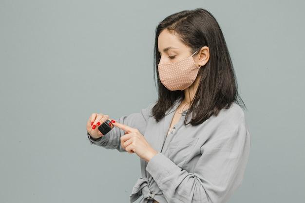 Photo femme dans un masque facial avec oxymètre de pouls sur son doigt, vérifie sa santé