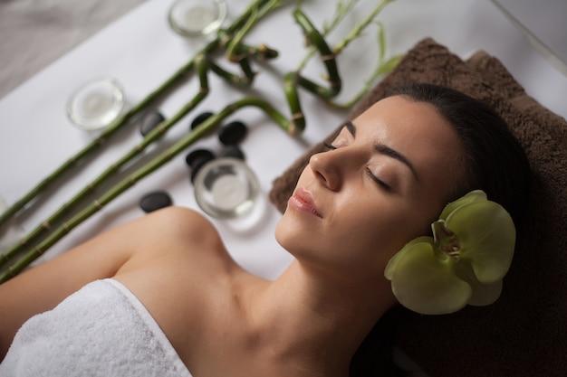 Photo d'une femme dans un salon spa allongé sur le bureau de massage