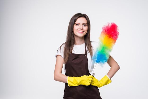 Photo de femme drôle de 20 ans portant des gants en caoutchouc jaune pour la protection des mains tenant un plumeau coloré tout en nettoyant la salle isolée