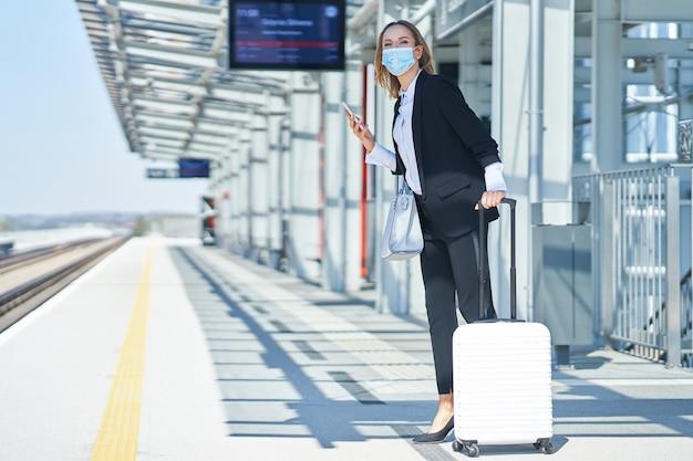 Photo d'une femme élégante portant un masque de protection marchant avec un sac et une valise dans la gare