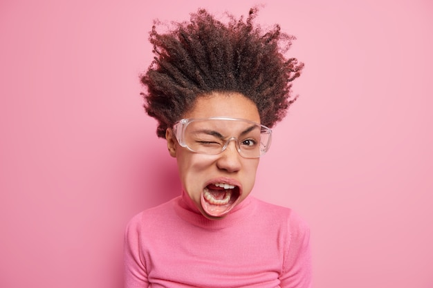 Photo d'une femme ethnique à la peau sombre et folle fait un clin d'œil garde la bouche ouverte a les cheveux bouclés relevés s'exclame fort habillé de façon décontractée