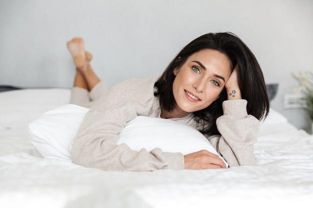 Photo de femme européenne des années 30 souriant, allongé dans son lit avec des draps blancs à la maison