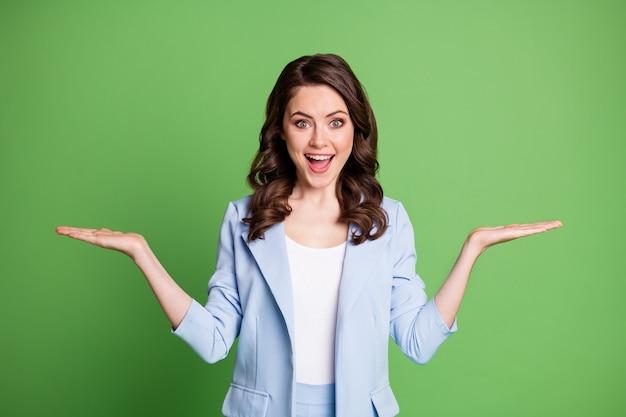 Photo de femme excitée deux bras paumes tenir un espace vide porter un blazer bleu isolé sur fond de couleur verte
