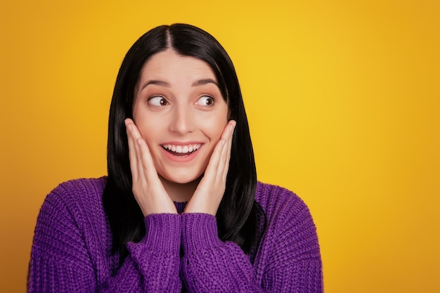 Photo d'une femme excitée regarde l'espace vide étonné surpris toucher mains joues vente porter un pull isolé sur fond de couleur vive