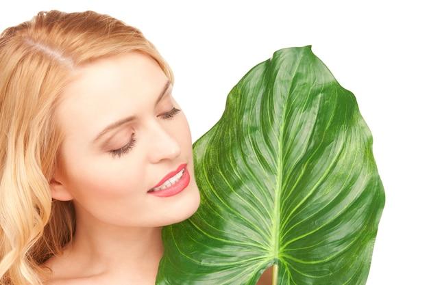 Photo de femme avec une feuille verte sur blanc