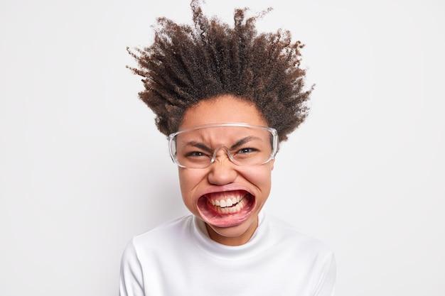 Photo d'une femme folle émotionnelle plisse les yeux le visage serre les dents a la bouche grande ouverte exprime la rage et la colère étant super folle porte des lunettes transparentes à col roulé