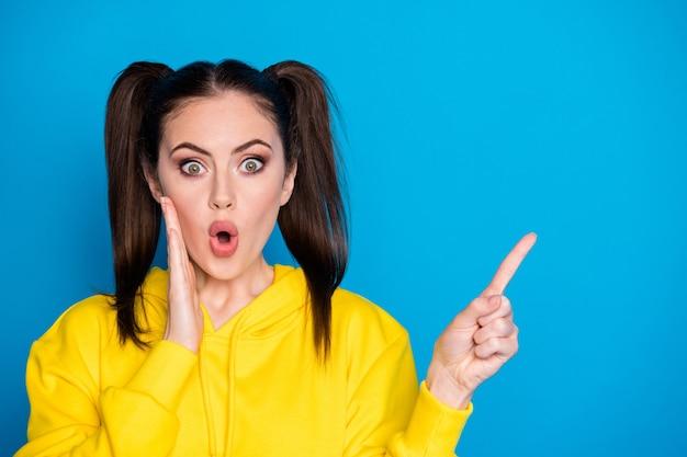 Photo d'une femme folle séduisante coiffure à deux queues côté doigt direct espace vide montrant une annonce de vente vendredi noir porter un pull à capuche jaune décontracté fond de couleur bleu isolé