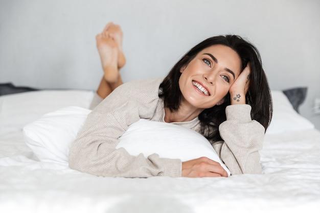 Photo de femme heureuse 30 s souriant, allongé dans son lit avec des draps blancs à la maison
