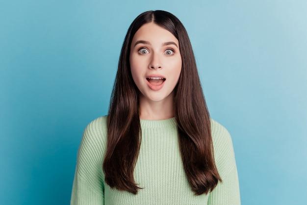 Photo de femme heureuse choquée bouche ouverte posant sur fond turquoise