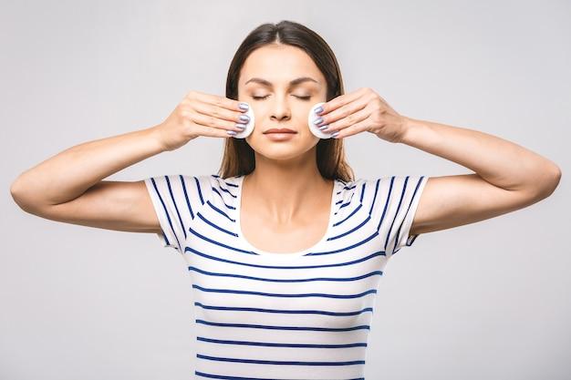 Une photo d'une femme heureuse nettoyant son visage avec des cotons