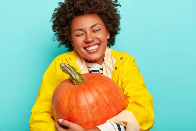 Photo d'une femme heureuse à la peau sombre embrasse la citrouille, a un sourire à pleines dents, porte un imperméable jaune, se sent heureuse et détendue, pose sur fond bleu.