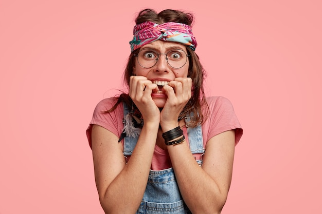 Photo D'une Femme Hippie Anxieuse Nerveuse Se Mord Les Ongles, Porte Un Bandeau Photo gratuit