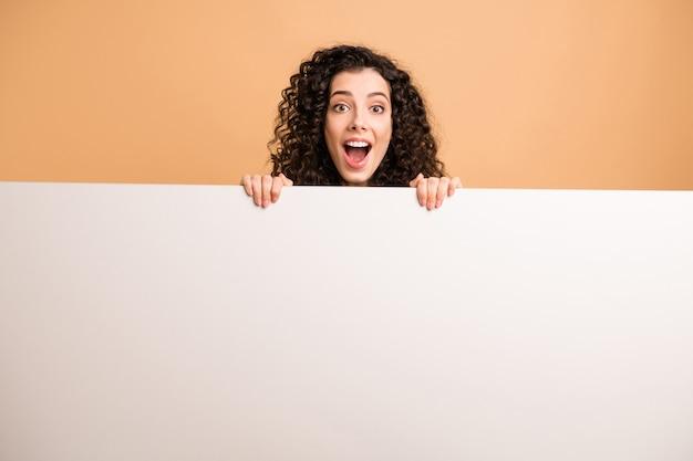 Photo de femme incroyable indiquant tenant les bras grande pancarte blanche présentant des informations de nouveauté porter des vêtements décontractés blancs fond de couleur pastel beige isolé