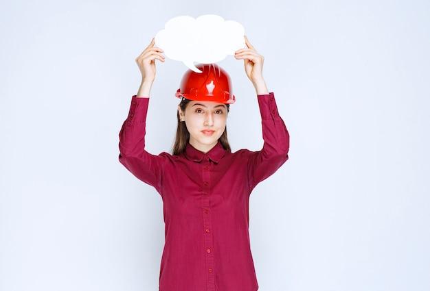 Photo d'une femme ingénieur en casque rouge tenant une bulle de dialogue vide sur fond blanc.