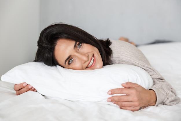 Photo de femme joyeuse 30 s souriant, allongé dans son lit avec des draps blancs à la maison