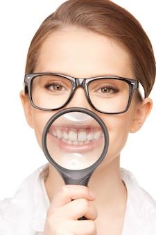 Photo de femme avec loupe montrant les dents