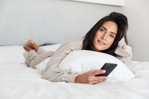 Photo d'une femme mature de 30 ans à l'aide de téléphone mobile, en position couchée dans son lit avec des draps blancs dans une pièce lumineuse