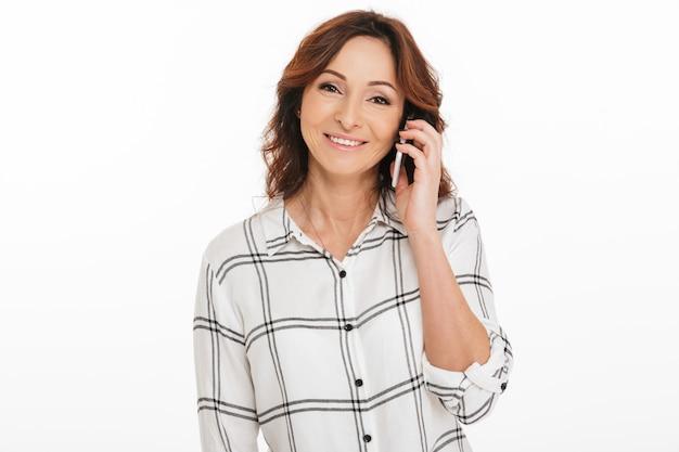 Photo de femme mature des années 40 en chemise à carreaux souriant tout en ayant une conversation mobile, isolé sur fond blanc en studio