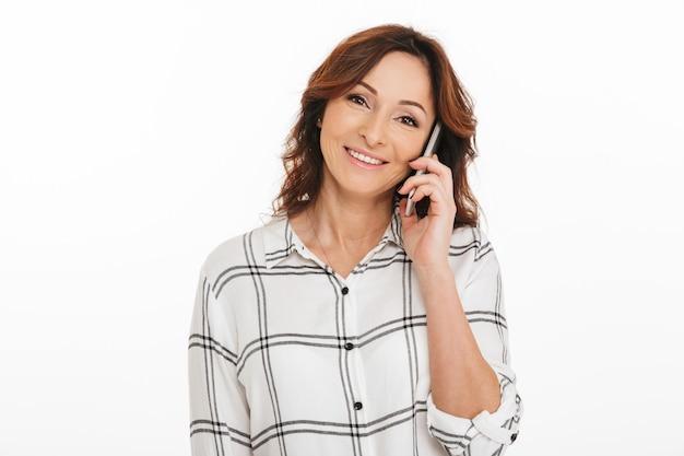 Photo de femme mature des années 40 en chemise à carreaux souriant tout en parlant sur smartphone, isolé sur fond blanc en studio