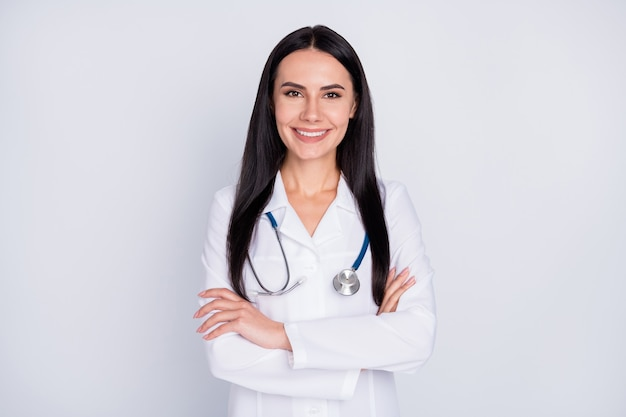 Photo de femme médecin croisant les mains sur fond gris