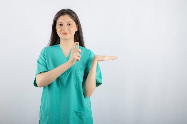 Photo de femme médecin avec un spray sur blanc.