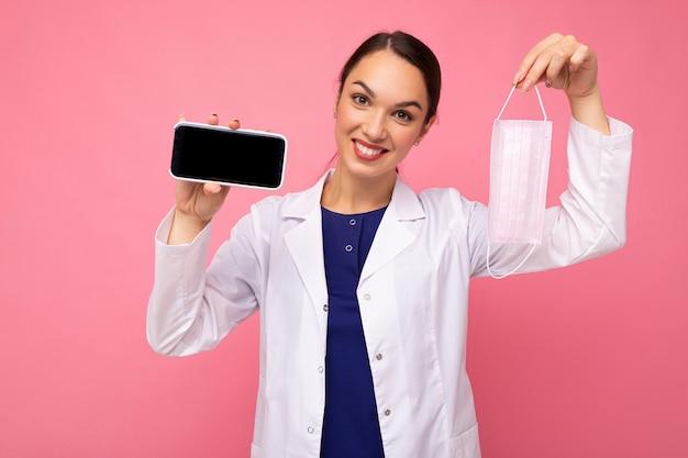Photo d'une femme médicale adulte souriante portant un manteau blanc tenant un masque montrant un mobile moderne