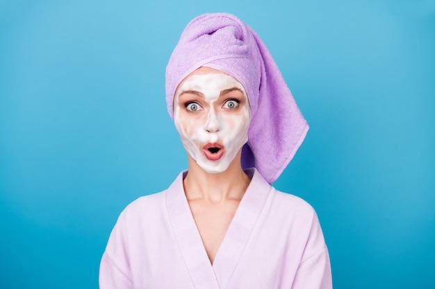 Photo de femme mignonne masque blanc en mousse bouche ouverte porter une serviette violette turban peignoir isolé fond de couleur bleu