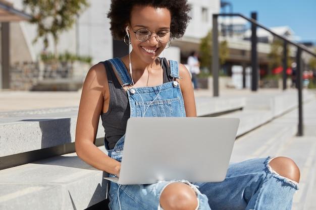 Photo d'une femme noire heureuse consulte des pages web, des claviers sur des commentaires ou des commentaires sur un ordinateur portable, écoute la diffusion en ligne dans des écouteurs, porte une salopette en lambeaux, fait du travail à distance, des modèles à l'extérieur