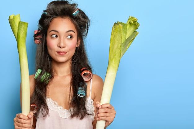 Photo d'une femme pensive aux cheveux longs foncés, porte des bigoudis pour avoir une coiffure frisée, vêtue d'une nuisette, porte deux poireaux frais