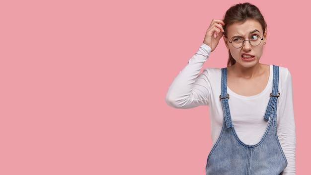 Photo d'une femme perplexe qui se gratte la tête avec perplexité, pense à trouver la bonne solution, porte un sarafan à la mode