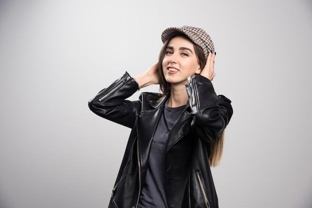 Photo d'une femme posant dans une veste en cuir noir et une casquette.