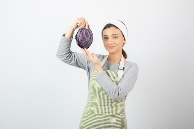 Photo de femme positive posant avec du chou violet sur blanc