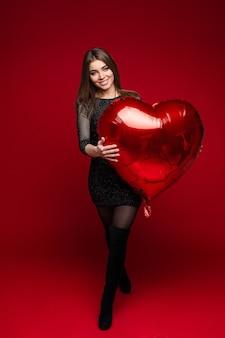 Photo de femme de race blanche en robe noire avec ballon coeur dans ses mains montre sa passerelle sur rouge