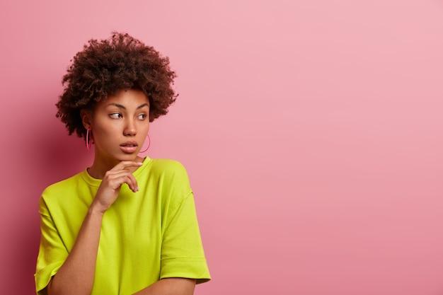 Photo d'une femme réfléchie avec des cheveux afro bouclés, garde la main sous le menton, a une expression pensive calme, porte un t-shirt vert décontracté, isolé sur un mur rose,