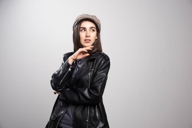 Photo d'une femme regardant ailleurs dans une veste en cuir noir et une casquette.