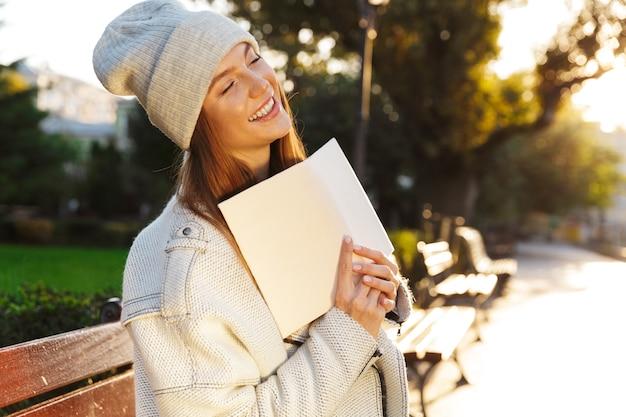 Photo d'une femme rousse assise sur un banc à l'extérieur tenant un livre.
