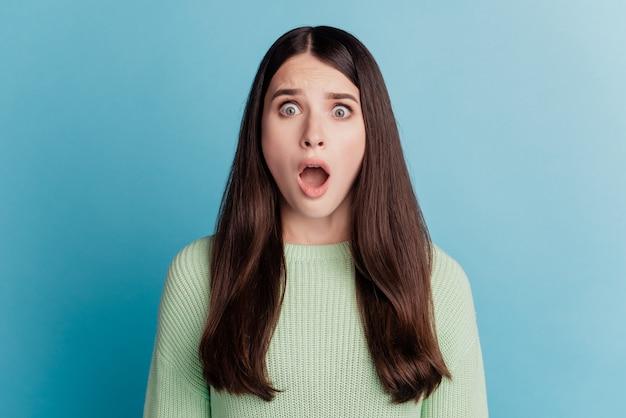 Photo d'une femme sans voix regardant la bouche ouverte posant sur fond turquoise