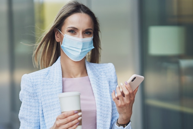 Photo d'une femme séduisante adulte portant un masque avec un smartphone marchant dans la ville