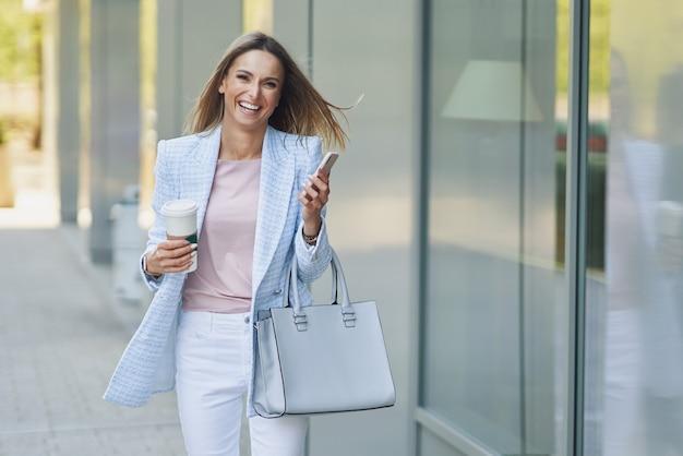 Photo d'une femme séduisante adulte avec un smartphone marchant dans la ville