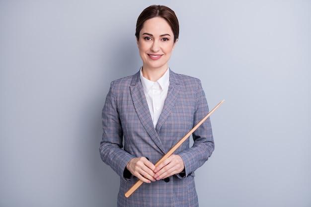 Photo d'une femme séduisante et confiante, de bonne humeur, enseignant expérimenté, regarder la caméra en ligne, leçon sur internet, tenir le pointeur porter une veste de costume à carreaux chemise isolée sur fond de couleur grise