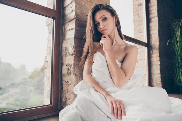 Photo d'une femme séduisante en quarantaine rester à la maison couverte de couverture blanche épaules nues sensuel se déshabiller petit ami appel vidéo toucher main menton taquiner mari s'asseoir près de la fenêtre à l'intérieur